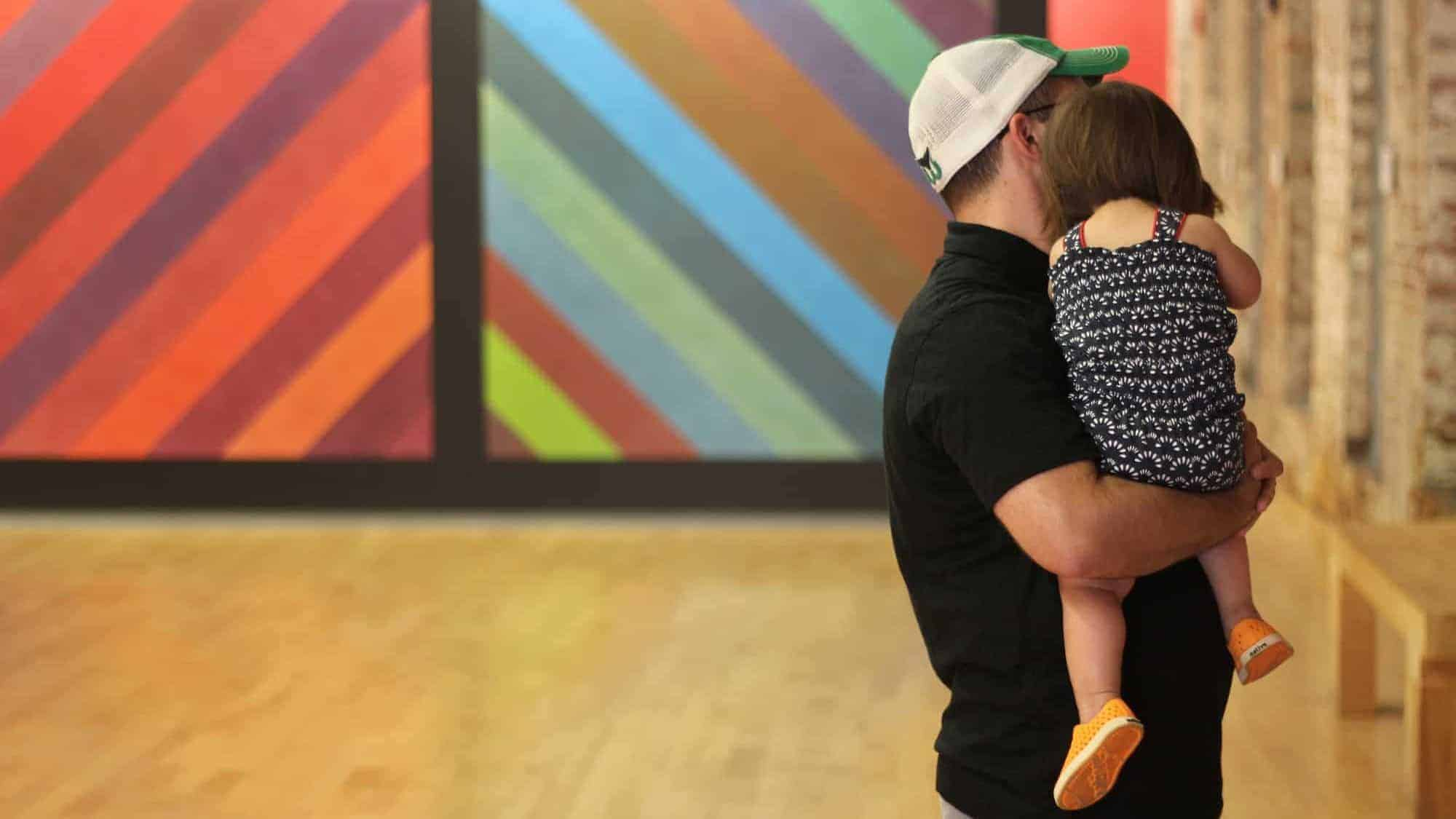 Visitors take in the bright color of Sol Lewitt's murals at Mass MoCA.