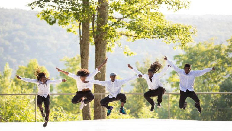 Dancers with Just Sole leap together on the Inside / Out Stage at Jacob's Pillow.
