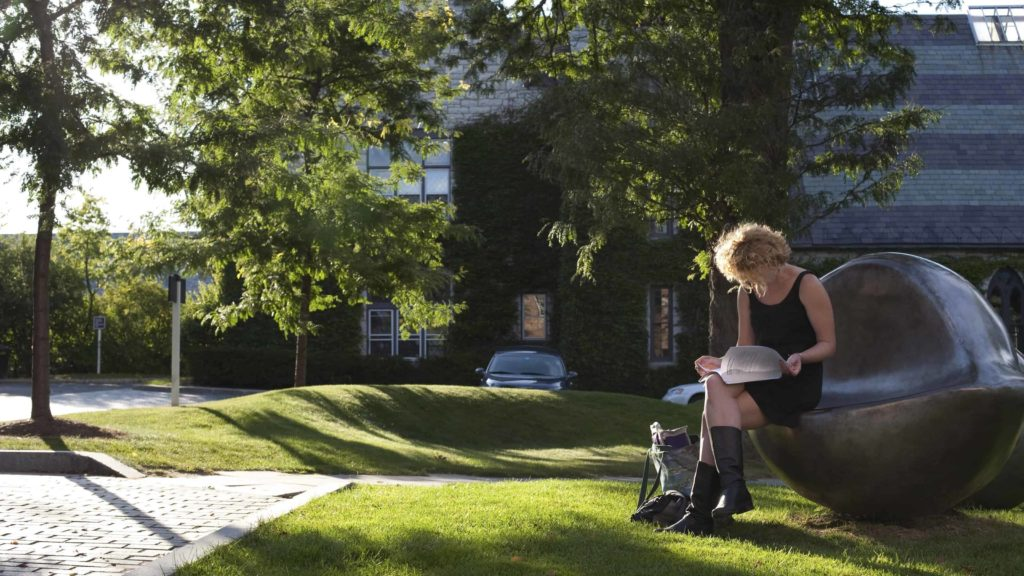 A reader sits on one of Louise Borgeois' giant glowing eye sculptures outside of the Williams College Museum of Art.