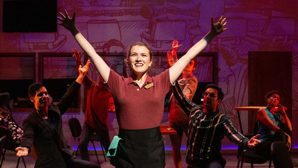 Actor Katie Birenboim stretches her arms wide, laughing, as the waitress with the cast of Berkshire Theatre Group's Working, the Musical.