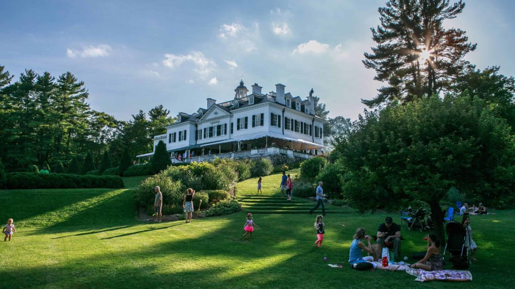 Families picnic on the lawn on a summer evening at the Mount, Edith Wharton's historic house in Lenox.