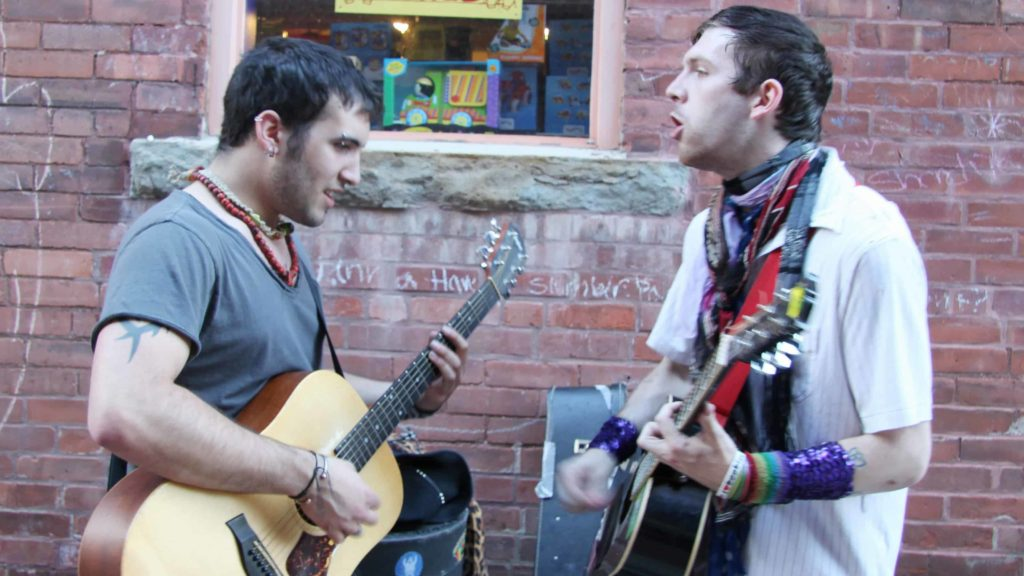 A guitar duo plays together on a Berkshire sidewalk on a warm night.